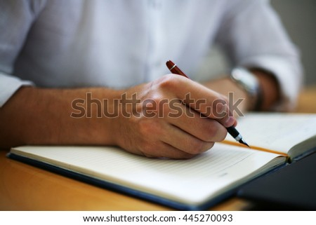 Indoor shot of an unrecognizable young Caucasian businessman working at his desk.