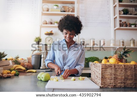 Indoor shot of attractive young woman chopping fruit to make a fresh juice. African female working at juice bar. - stock photo