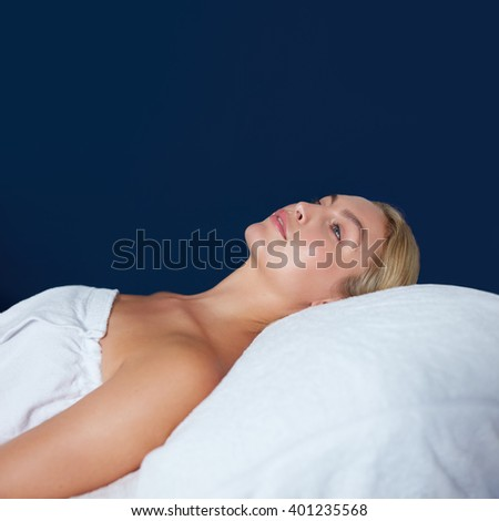 Indoor shot of attractive young woman lying on massage table. Caucasian woman wrapped in white towel lying on bed looking away. - stock photo
