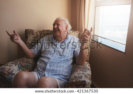 Indoor shot of happy old man sitting on a arm chair and  smiling. Senior man relaxing at old age home. - stock photo