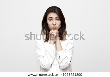 Indoor shot of regretful woman looks gloomy and desperate, keeps hands together, beggs for forgiveness for betray, feels sorry and guilty. Cute adorable girl pleads about something