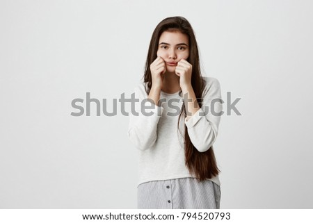 Indoor shot of sad dark-eyed pretty brunette woman making grimace blowing her cheeks and pulling them pretending to have fun. Beautiful girl dressed in casual clothes being offended