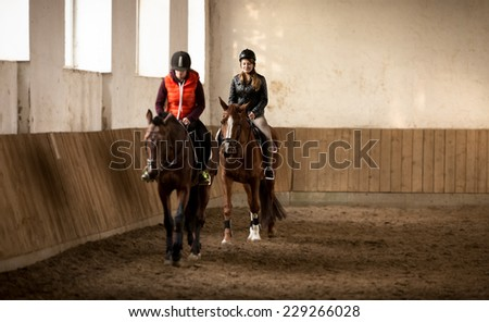 Indoor shot of two woman jockeys doing training in riding hall - stock photo