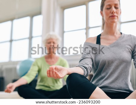 Indoor shot of women mediating in yoga class. Focus on hand. Relaxed fitness women practicing yoga at gym. - stock photo
