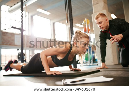 Indoor shot of young female exercising with personal trainer at gym. Fitness woman doing push ups with her personal trainer at health club. - stock photo