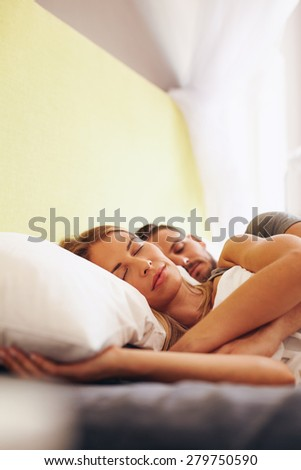 Indoor shot of young man and woman sleeping together in bedroom. Young caucasian couple sleeping on bed. - stock photo