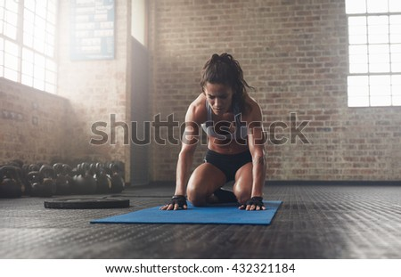 Indoor shot of young woman doing a forward bend exercise on fitness mat. Muscular young athlete doing pilates workout at the gym. - stock photo