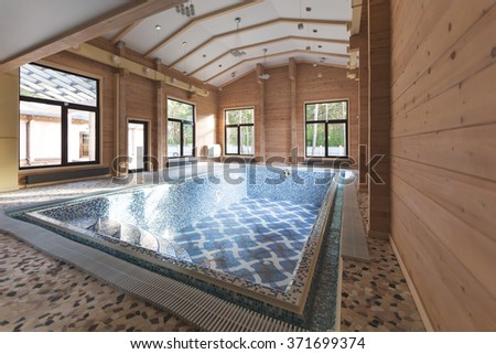 Indoor swimming pool in wooden eco house. Interior of new house built from cedar. - stock photo