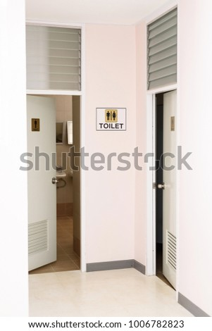 Indoor toilet, women and men logo on the wall.