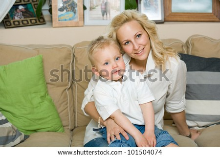 Indoors portrait of pretty young mom and her cute kid son. - stock photo