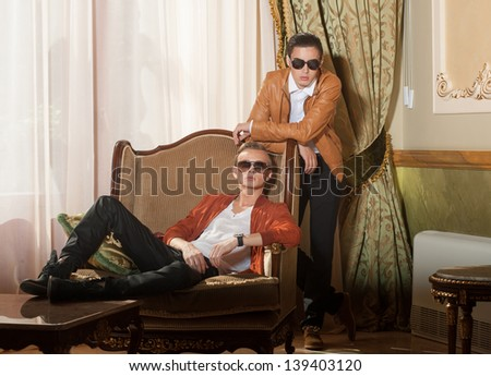 Indoors portrait of two young men in sunglasses - stock photo