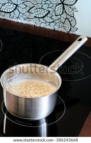 Induction stove, pot with porridge on it.