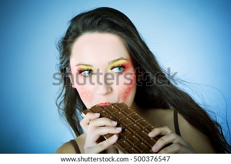 Indulging in a sweet affair with chocolate. Close-up of a beautiful women holding finger on her red lips while standing against grey background. Girl with chocolate. Beautiful portrait.