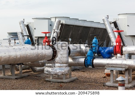 Industrial air conditioner and pipes on the roof - stock photo