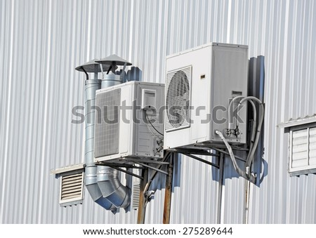 Industrial air conditioning and ventilation systems on a wall - stock photo
