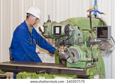 Industrial area. The mechanic works at the lathe. - stock photo