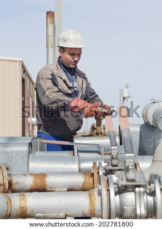 Industrial area. Worker closes the valve on the oil pipeline. - stock photo