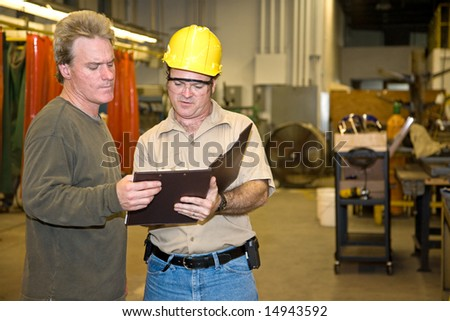 Industrial auditor discussing his inspection results with the factory owner. - stock photo