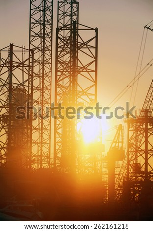 Industrial background: Closeup of shipyard construction site with silhouettes of cranes and steel structures against rising sun. - stock photo