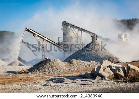 Industrial background - crusher (rock stone crushing machine) at open pit mining and processing plant for crushed stone, sand and gravel - stock photo
