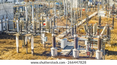 industrial background of high voltage substation on yellow dry grass backdrop Power circuit breaker in substation Disconnecting switch on high-voltage Step-down or step-up transformer - stock photo