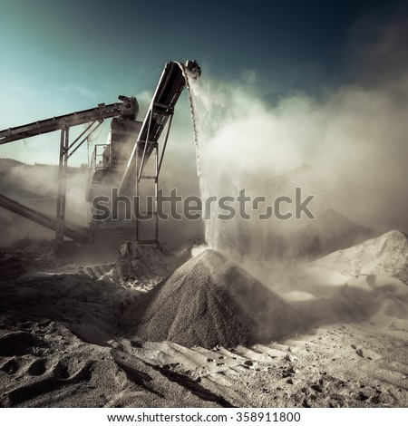 Industrial background with working gravel crusher - stock photo