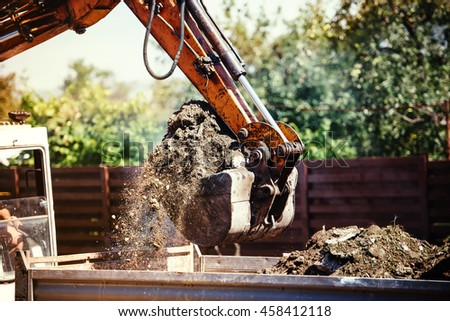 industrial backhoe excavator moving earth on construction site - stock photo