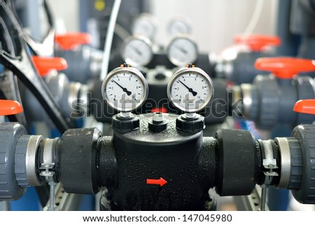 industrial barometers and water pipes in boiler room - stock photo