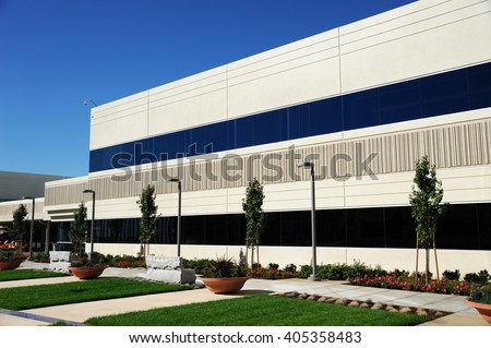 industrial building exterior and green tree in spring