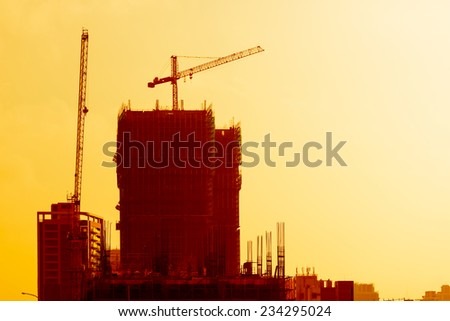 Industrial building site at sunset with cranes on an office or apartment block under construction silhouetted against a colorful orange sky - stock photo