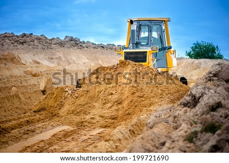 industrial bulldozer and excavator working with earth in sandpit on highway construction site - stock photo
