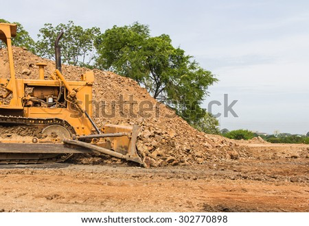 industrial  bulldozer moving earth and sand in sand pit or quarry - stock photo