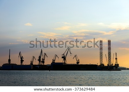 Industrial cargo cranes in the dock - stock photo