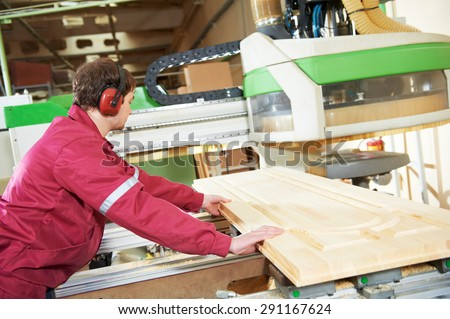 industrial carpenter worker operating wood cutting machine during wooden door furniture manufacturing - stock photo