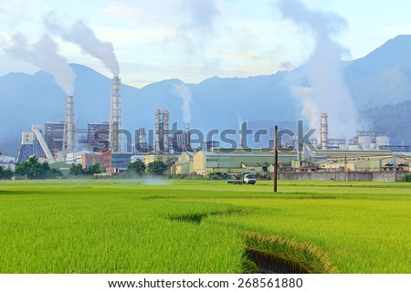 Industrial chimneys of a chemical factory in the middle of a green rice field emitting smoke on a cloudy morning ~ Factory pipes polluting air on a silent morning ( environmental problem ) - stock photo