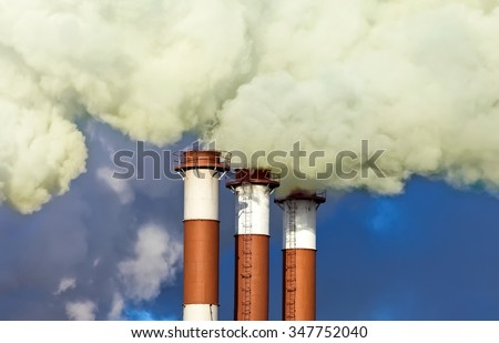 Industrial chimneys with smoke over blue sky - stock photo