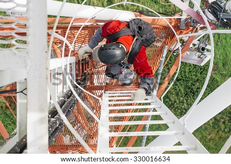 Industrial climber climbs the telecommunications tower. tower technician with a backpack on his shoulders climbs the telecommunication tower, top view