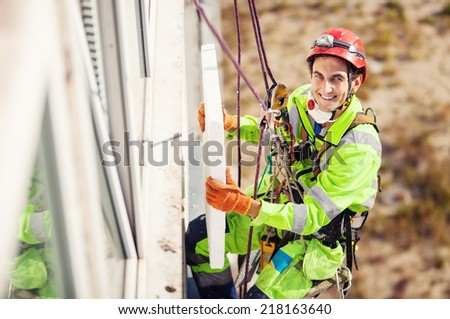 Industrial climber placing a polyfoam sheet insulation to the wall on a building - stock photo
