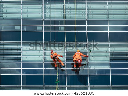 Industrial climbers wash windows in a building. Alpinism.