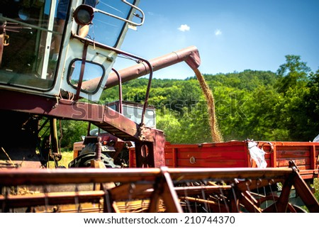 industrial combine harvester unloads wheat grain in tractor trailer - stock photo