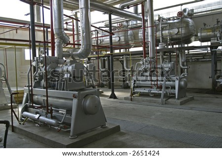 industrial compressors and pipe work in factory - stock photo