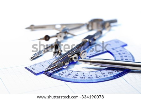 Industrial concept. Drawing instrument and pen on graph paper - stock photo