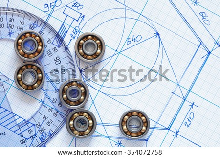 Industrial concept. Few ball bearings near ruler on graph paper background - stock photo