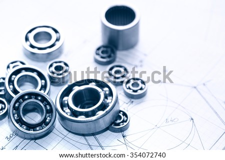 Industrial concept. Few ball bearings on graph paper background - stock photo