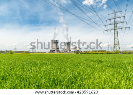 Industrial Concept - Nuclear Industrial power plant with green field. Nuclear power plant is a thermal power station in which the heat source is a nuclear reactor  - stock photo
