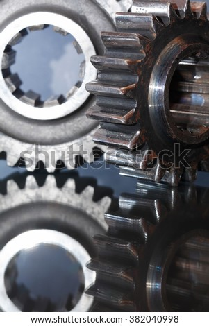Industrial concept. Two old gears on glass surface with reflection