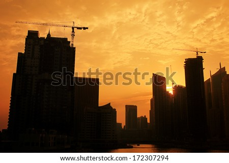 industrial construction crane against sunset in Dubai city - stock photo