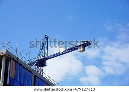 Industrial Construction Crane and building against sunlight and blue sky background.