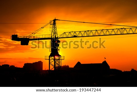 Industrial construction crane and buildings silhouettes over sun at sunrise - stock photo