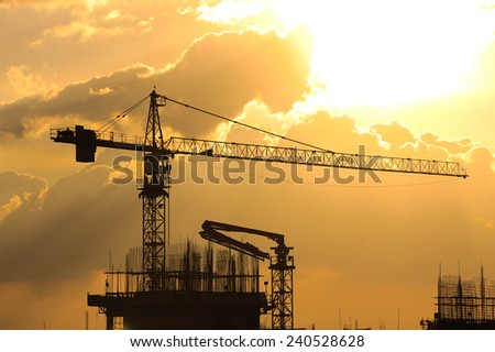 Industrial construction crane on sunset in a building site - stock photo